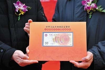 12月28日,人民银行在第一套人民币发行地——河北石家庄举行人民币发行70周年纪念钞首发仪式,并将J000000001号纪念钞交由当地河北钱币博物馆临时展出。新华社记者