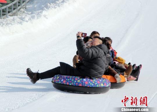 游客体验滑雪圈运动并自拍。