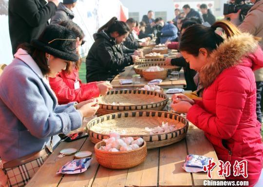 1月13日,正值中国传统节日腊八节,图为游客正在进行剥蒜比赛。