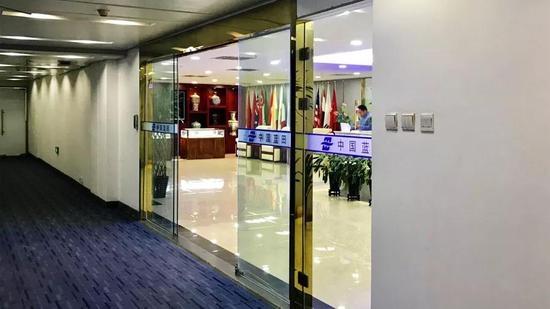 中国蓝田总部,大厅内设有玉石、瓷器展柜,还有多国国旗。